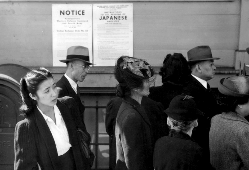 Japanese Americans in front of posters with internment orders in 1942.