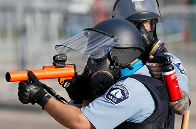 Minneapolis police officers point a rubber bullet gun and mace