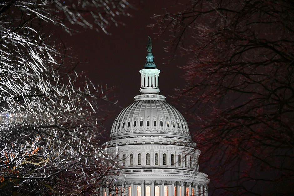 The U.S. Capitol is seen through ice-covered tree branches.