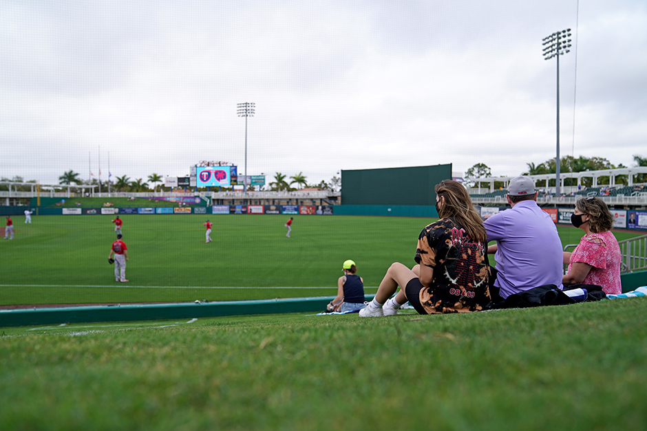 Fans watch from a grassy berm in right field prior to the spring training game between the Minnesota Twins and the Boston Red Sox in Fort Myers, Florida.