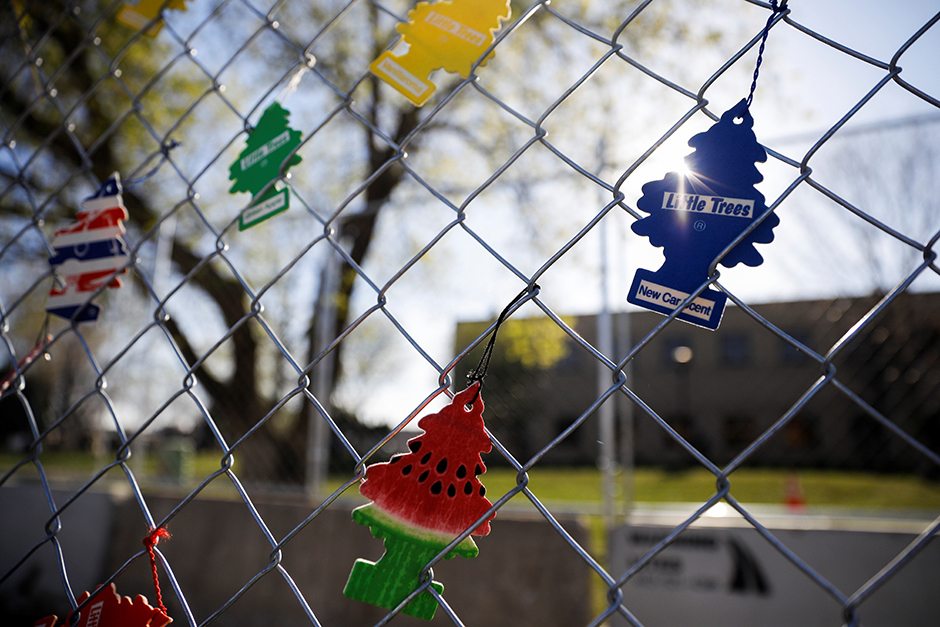 Air fresheners are seen hanging from a fence as people gather outside the Brooklyn Center Police Department to demand justice days after former police officer Kim Potter fatally shot Daunte Wright.