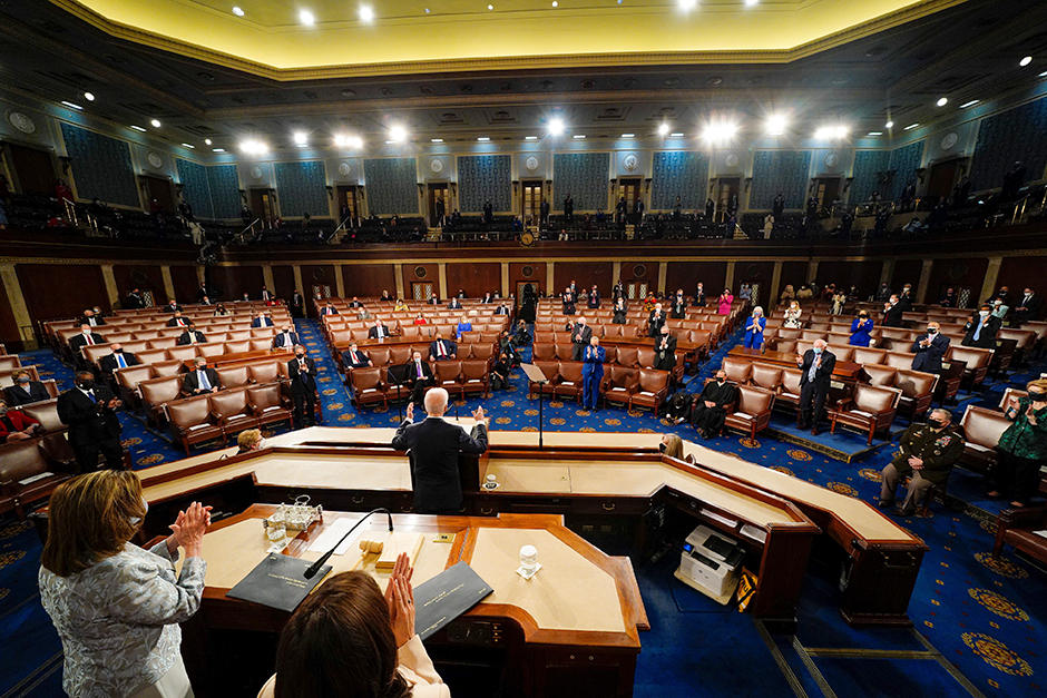 President Joe Biden addressing a joint session of Congress, with Vice President Kamala Harris and House Speaker Nancy Pelosi on the dais behind him.