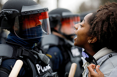 A demonstrator confronting police during a protest