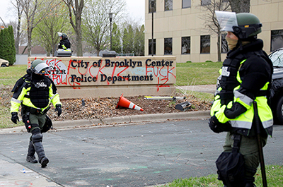 Police officers stand guard outside the Brooklyn Center Police Department
