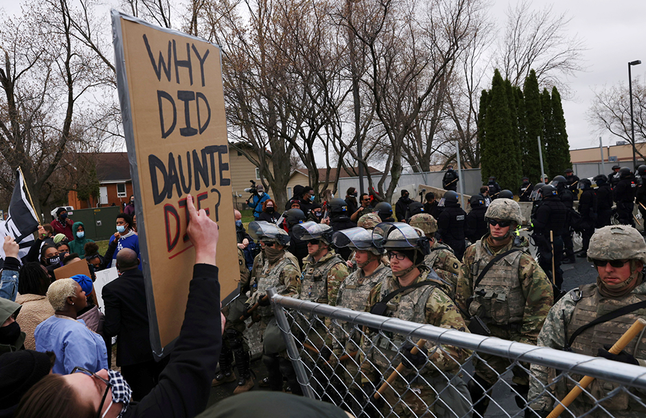 Protesters rallying outside the Brooklyn Center Police Department, guarded by members of the police and National Guard, a day after Daunte Wright was shot and killed by a police officer.