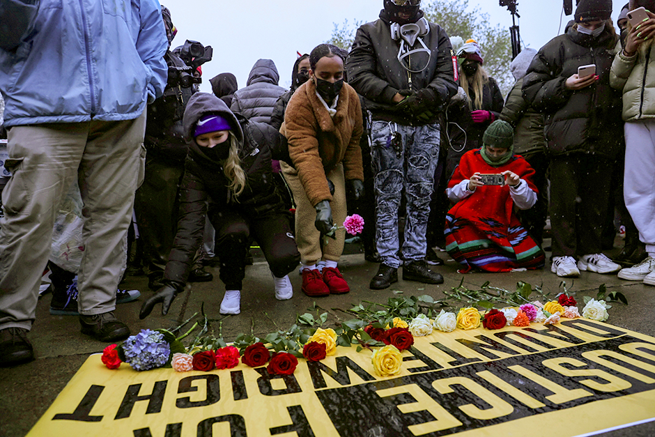 People lay flowers on a sign as they rally outside the Brooklyn Center Police Department, days after Daunte Wright was shot and killed by a police officer.