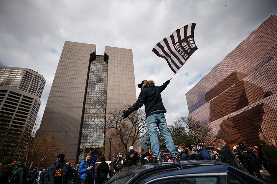 A person standing on a car waves a flag after the verdict in the trial of former Minneapolis police officer Derek Chauvin, in front of Hennepin County Government Center.