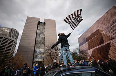 A person standing on a car waves a flag
