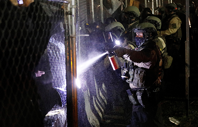 A sheriff's deputy uses pepper spray at the fenced up perimeters of the Brooklyn Center Police Department, as protests continue days after former police officer Kim Potter fatally shot Daunte Wright, in Brooklyn Center.