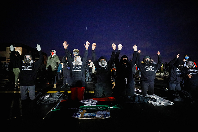 Activists raising their arms as they confront state troopers, National Guard members and other law enforcement officers following a march on Tuesday night.