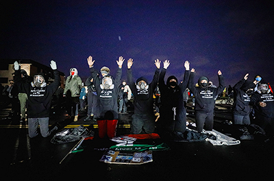 Activists raising their arms as they confront state troopers, National Guard members and other law enforcement officers