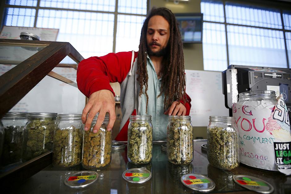 Volunteer Charlie Kirchheimer displaying jars of dried cannabis buds at the La Brea Collective medical marijuana dispensary in Los Angeles, California.