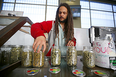 Charlie Kirchheimer displaying jars of dried cannabis buds