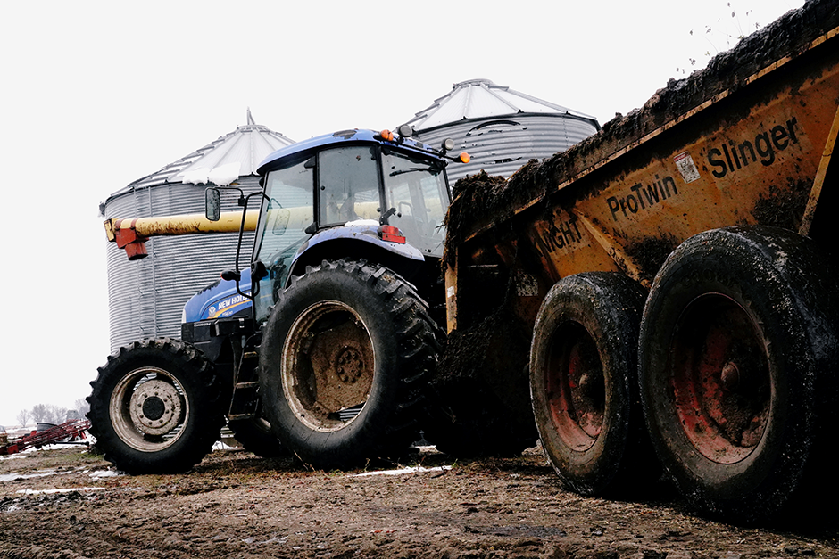 A tractor pulling a manure spreader is seen on an organic dairy farm in Belle Plaine.