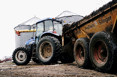 A tractor pulling a manure spreader