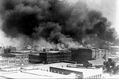 Smoke rises from buildings during the race massacre in Tulsa