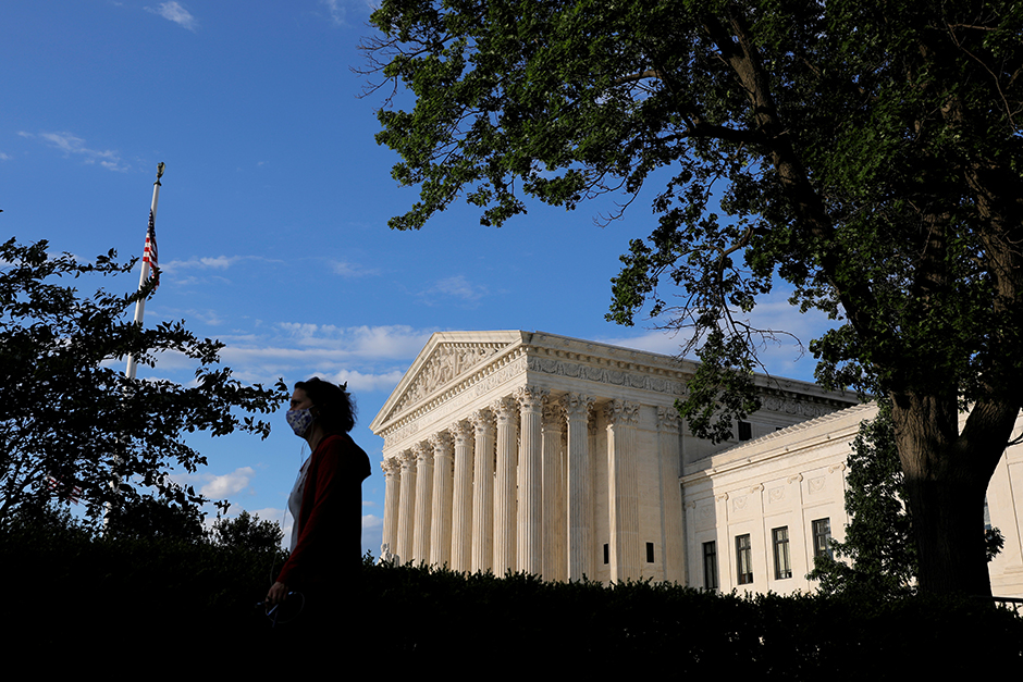 A person in a mask walks past the United States Supreme Court Building in Washington, D.C., on May 13, 2021.