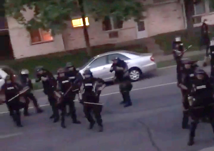 A still image from a video of officers patrolling a Minneapolis neighborhood. Officers yell at a woman standing on her porch to go back inside before firing paint rounds at her home.