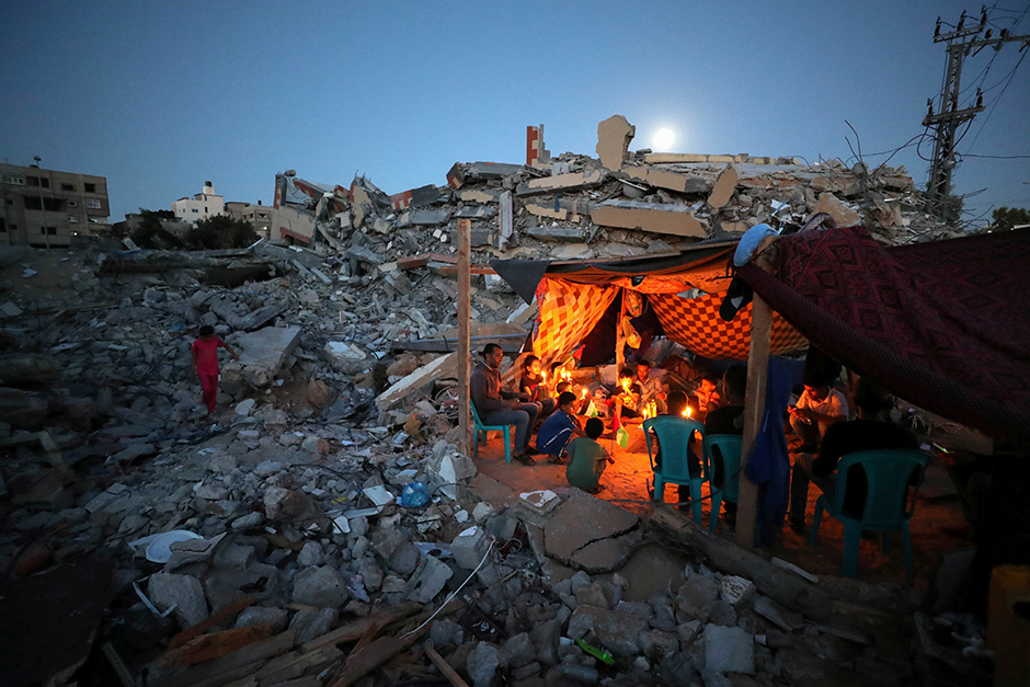 Palestinians hold candles as they sit in a makeshift tent amid the rubble of their houses which were destroyed by Israeli air strikes during the Israeli-Palestinian fighting in Gaza on May 25.
