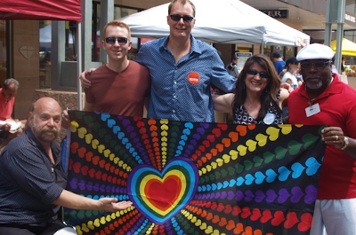 photo of people holding a rainbow heart flag at a parade