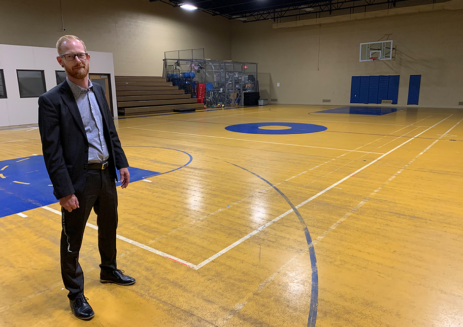 Adam Hammer, Alexandria College's director of marketing and communications, pictured in the gymnasium that is being renovated for the school's new volleyball program.