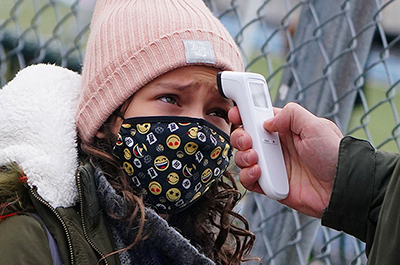 A child has their temperature checked