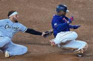 Chicago White Sox third baseman Yoan Moncada tagging out Minnesota Twins first baseman Miguel Sano
