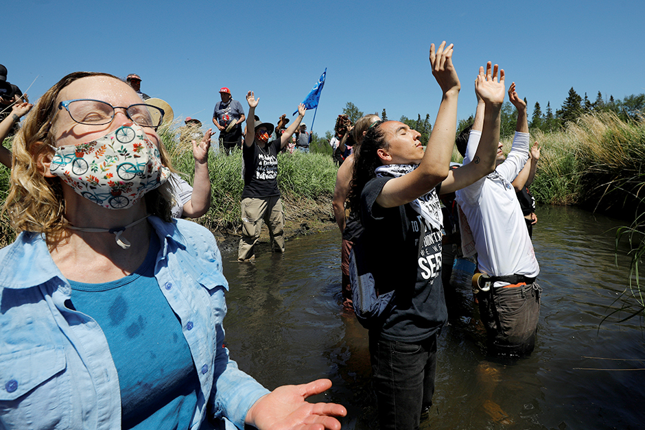 Indigenous leaders and activists participating in a prayer at the Mississippi headwaters in Solway on June 7.