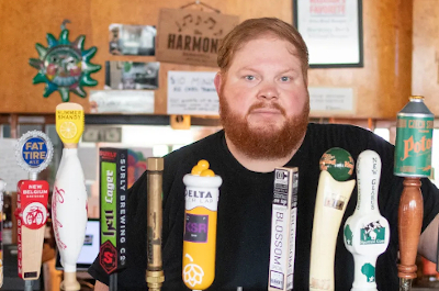 photo of man standing behind beer taps at a bar