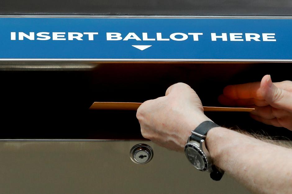 photo of hands putting sample ballot into ballot dropbox slot