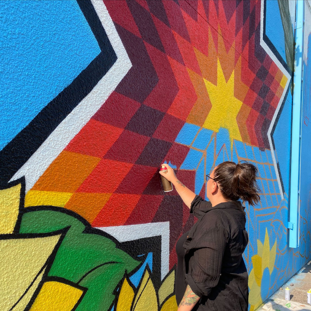 photo of artist painting colorful mural