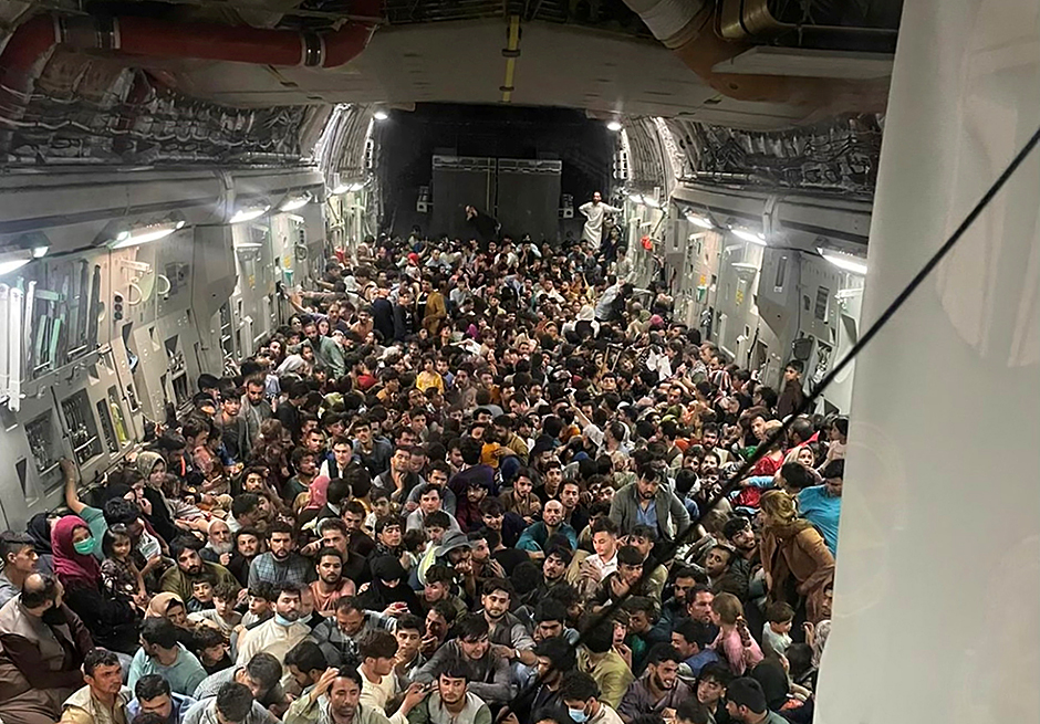 Evacuees crowd the interior of a U.S. Air Force C-17 Globemaster III transport aircraft, carrying some 640 Afghans to Qatar from Kabul, Afghanistan, on Sunday.