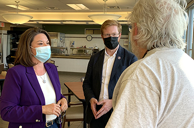 Rep. Angie Craig and Rep. Peter Meijer shown visiting a veterans home in Hastings.