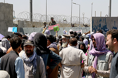 Crowds of people show their documents to U.S. troops outside the airport
