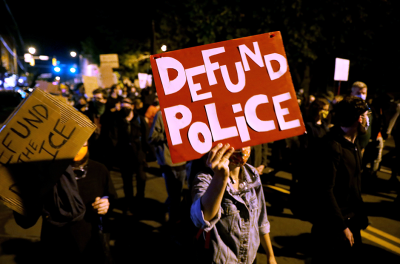 """Demonstrators hold a sign reading """"Defund the police"""" during a protest in Rochester, New York, over the death of a Black man, Daniel Prude, after police put a spit hood over his head during an arrest on March 23, 2020."""
