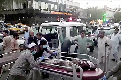 people carrying an injured person to a hospital after an attack at Kabul airport