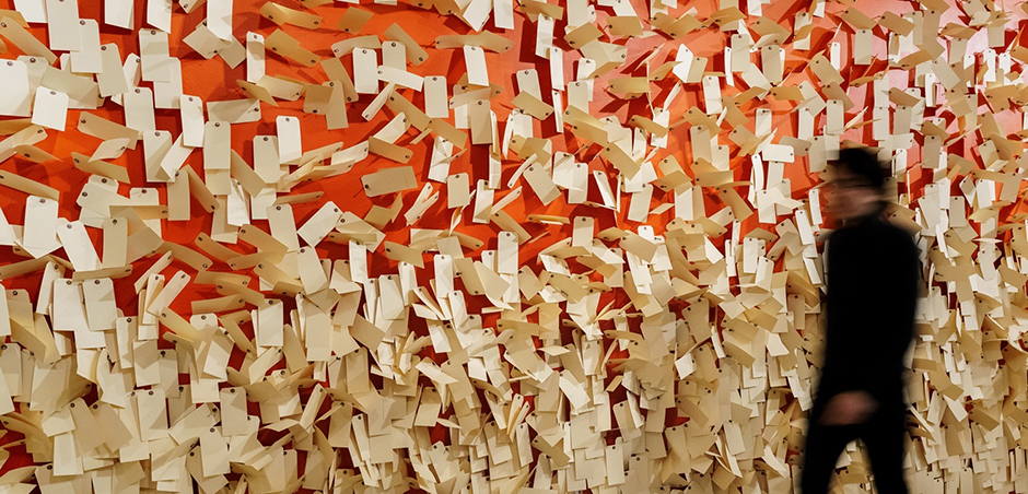 The back wall of the Osher Gallery is painted red and covered with thousands of manila tags, like the ID tags children wore on the trains.