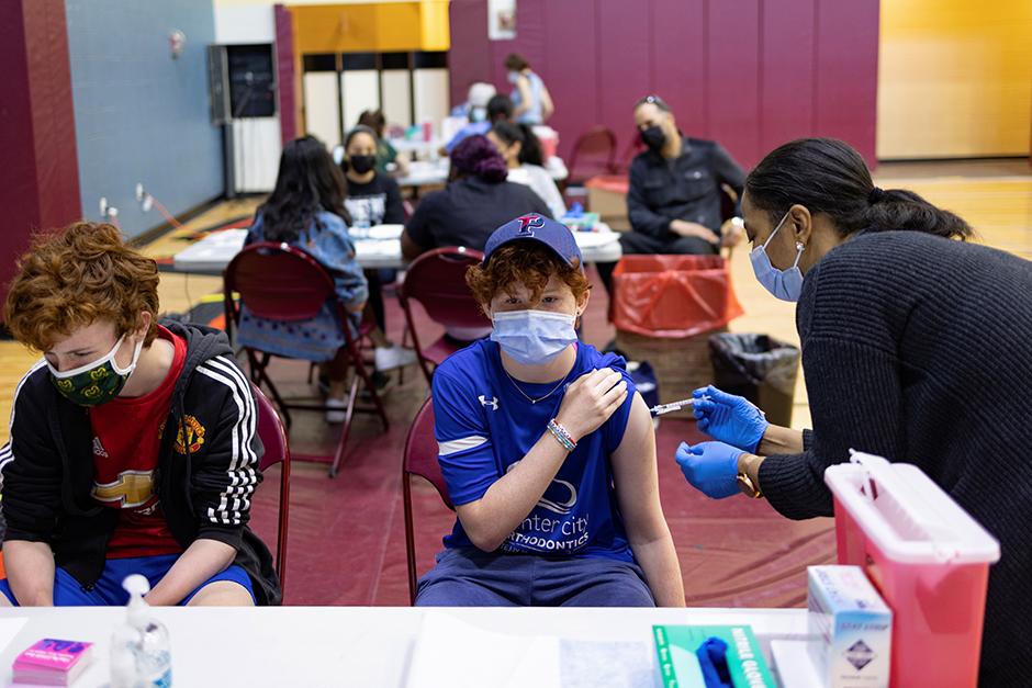 Teenagers receiving the coronavirus disease vaccine at a high school gym in Philadelphia.