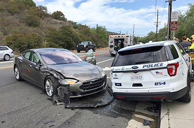 A Tesla sedan is shown after it struck a parked Laguna Beach Police Department vehicle