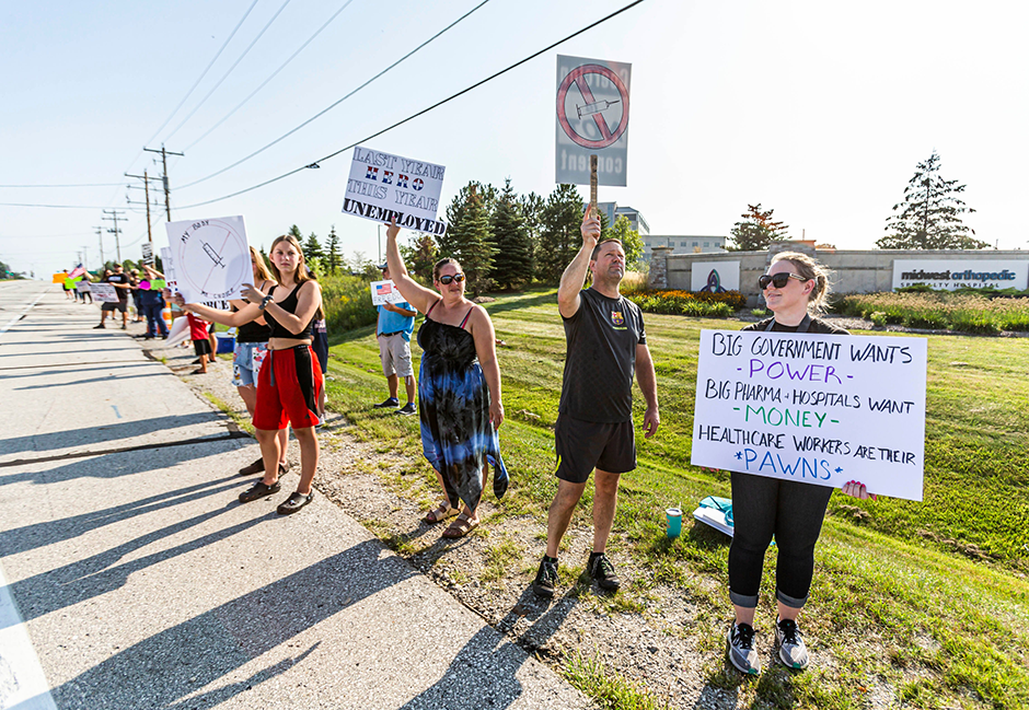 Protesters hold up signs in front of Ascension SE Wisconsin Hospital in Franklin, Wisconsin, during a rally against mandatory vaccination of employees on Aug. 27, 2021.