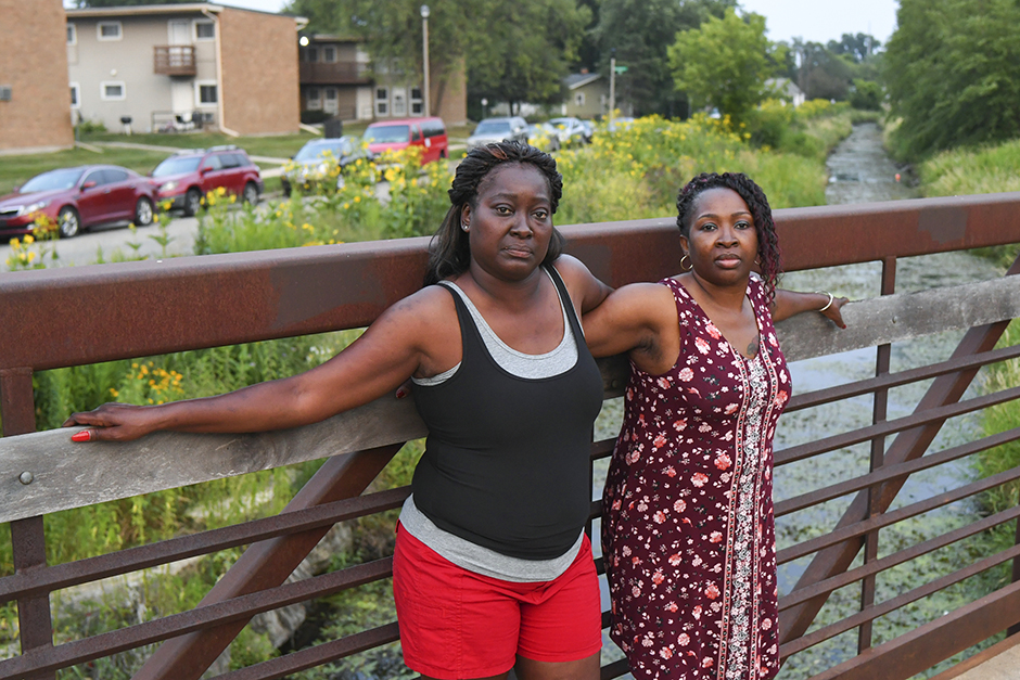 Melody Homesly, left, and Carnetta Galvin stand on a bridge that crosses Starkweather Creek near Galvin's home of 16 years in the Darbo-Worthington neighborhood of Madison, Wisconsin.