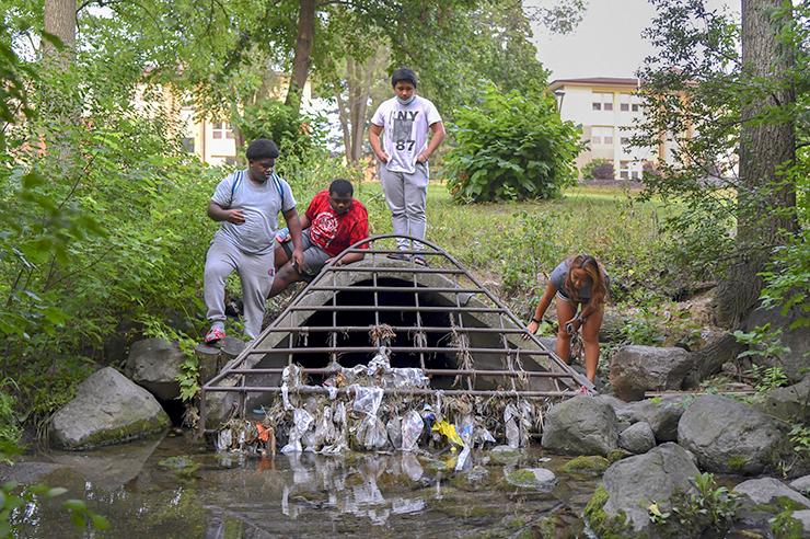 From left, Truax neighborhood teenagers Mack Rimson, 18, Elijah Smith, 16, James Xiong, 15, and Pau Xiong, 19, stand on a storm drain near Starkweather Creek.