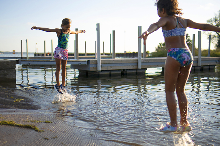Stoni Hawkins, left, and Terriyah Moss play in Starkweather Creek at the Olbrich Park boat launch in Madison.