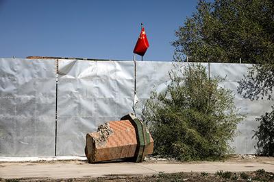 A broken-off minaret of Xinqu Mosque lies near a Chinese national flag