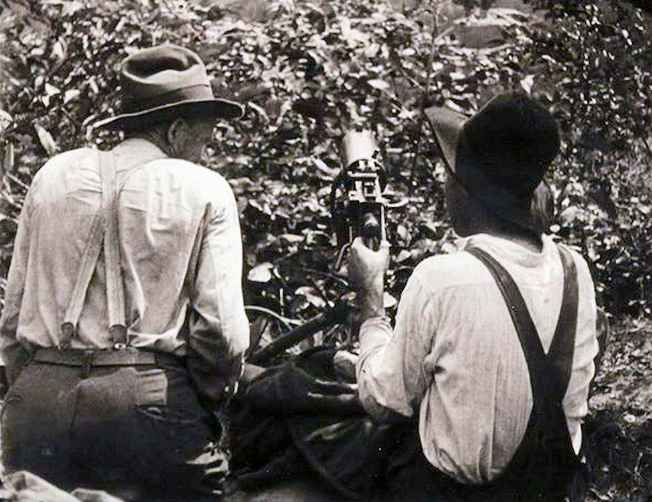 Two coal miners sit in a sniper's nest with a machine gun during the Battle of Blair Mountain in 1921.