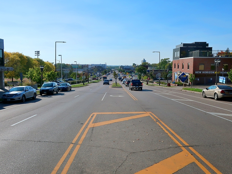 The photo shows a 5-lane divided road with cars parked on either side and a grassy street in the middle, sloping downhill in the distance