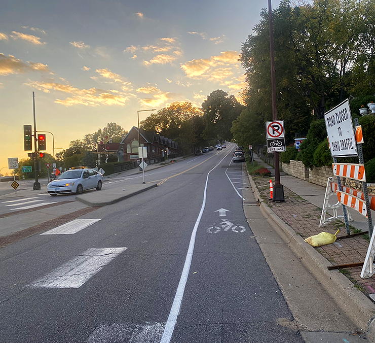 Road photo taken at sunset with the bike lane on the right side of the road in the center of the photo