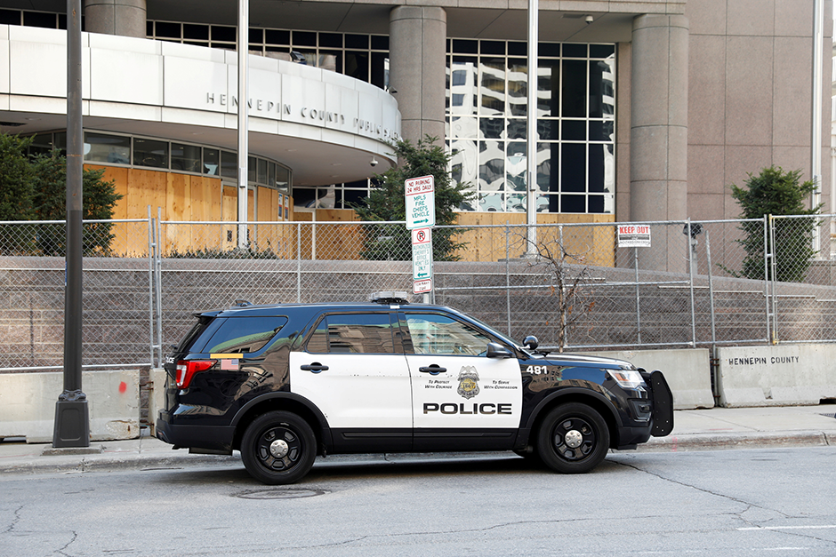 A Minneapolis Police Department vehicle parked near the boarded-up Hennepin County Public Safety Facility.