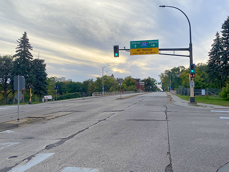 The picture shows the green light on the stop light at the intersection and the broad four-lane road with cracked pavement
