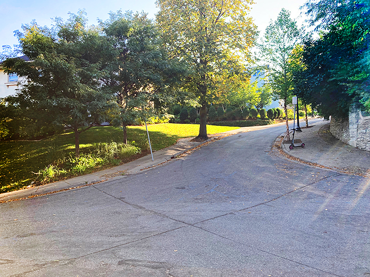 The photo shows a small side road sloping upward at a dramatic angle